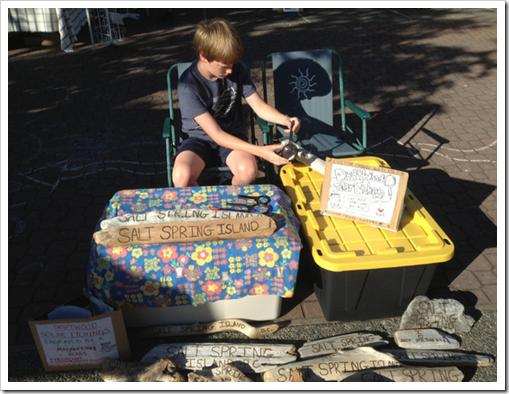 虫眼鏡で流木に文字を彫る爽やか太陽少年(カナダ)