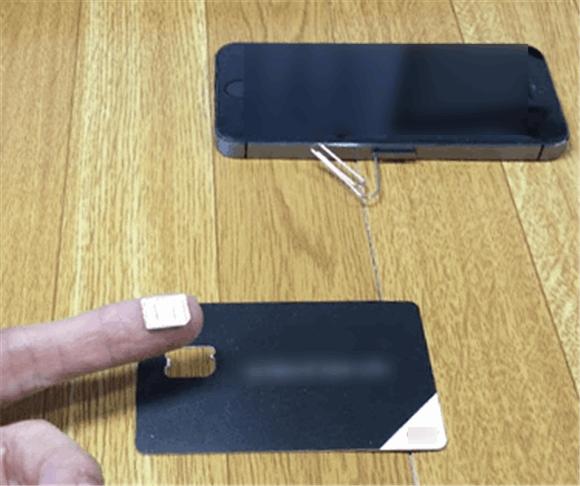 SIMカードをiPhoneに装填しているところ。