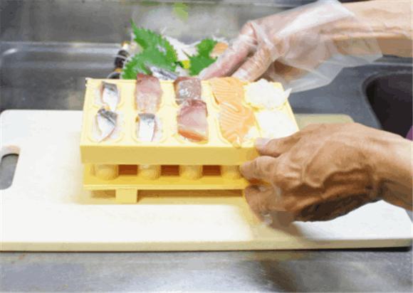 「とびだせ!おすし」の使い方4.お寿司の型枠を持ち上げて、押し型の上に置き、押し下げます。