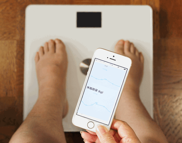 Wi-Fiに対応したスマホ連携 体重計で体重を測定しiPhoneで体重の推移を把握している女性の足。